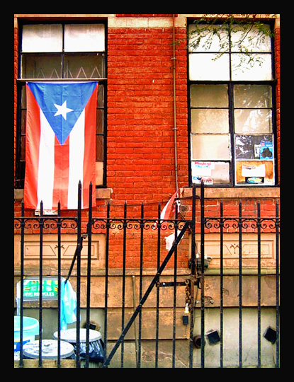 A Puerto Rican flag hanging in an East Harlem apartment window (Flickr/Richard Alexander Caraballo)